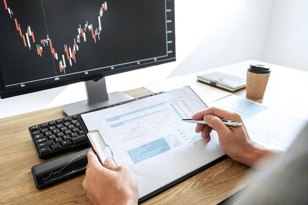 컴퓨터와 함께 작업하고 주식 차트 데이터로 그래프 주식 시장 거래를 분석하는 사업가