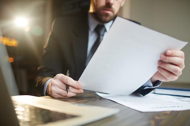 Бизнесмен работает с документацией на стол