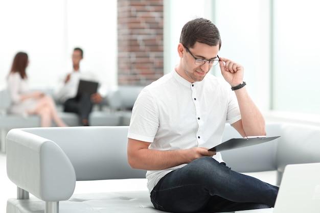 비즈니스 센터의 로비에 앉아 문서 작업 사업가. 사람과 기술