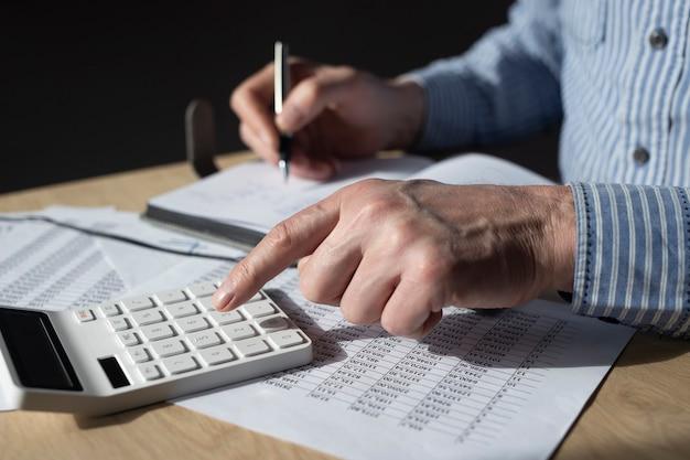 財務書類、会計統計を扱うビジネスマン。税計算と予算の概念。