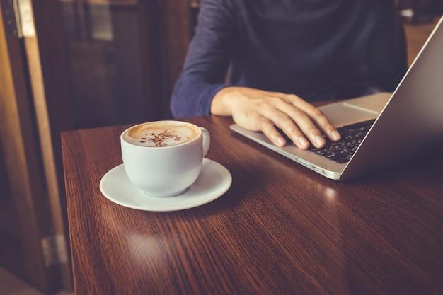 카페의 책상 테이블에 노트북과 커피 컵을 가지고 일하는 사업가