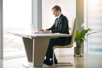 モダンなデスクでノートパソコンを操作するビジネスマン