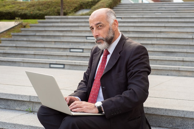 Businessman working with laptop computer on street