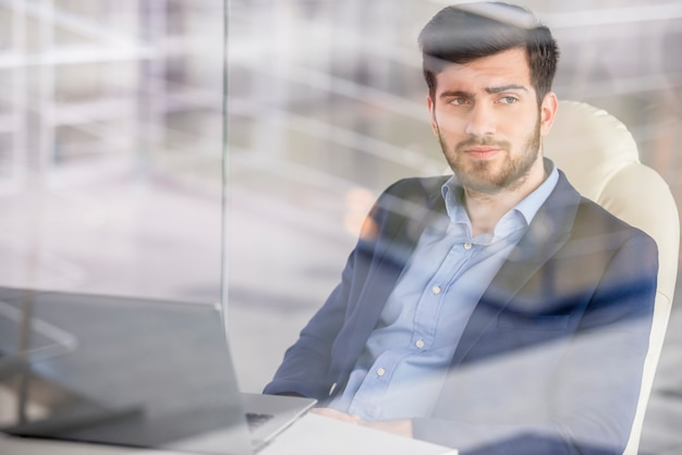 Businessman working with laptop in office.