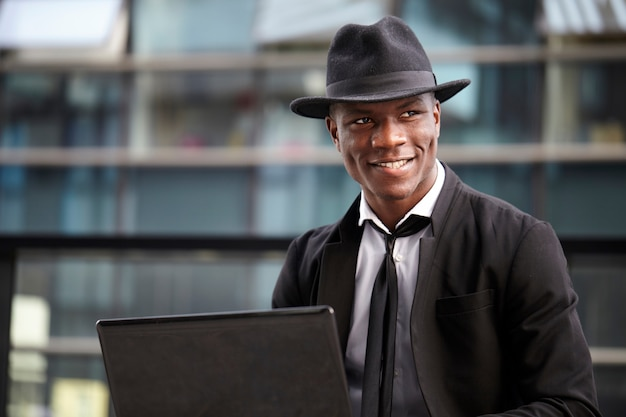 Businessman working with mobile and  laptop in urban environment