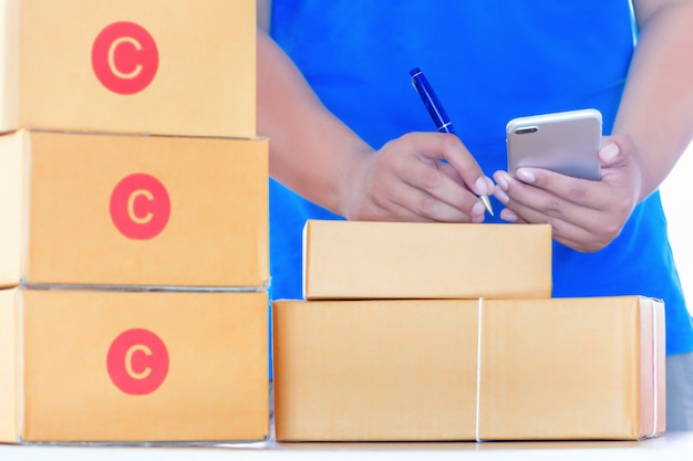 Businessman working with mobile phone and packing brown parcels box at home office.