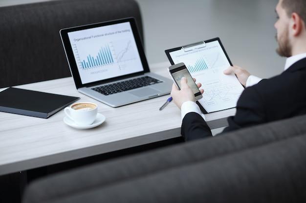 スマートフォンを使用して新しいスタートアッププロジェクトに取り組んでいるビジネスマン。