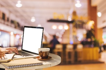 Businessman working with of laptop with blank screen and coffee in coffee shop like.