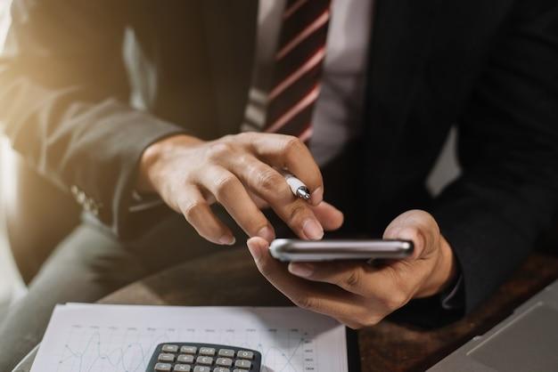 Бизнесмен, работающий с умным телефоном и ноутбуком и цифровым планшетным компьютером в домашнем офисе.