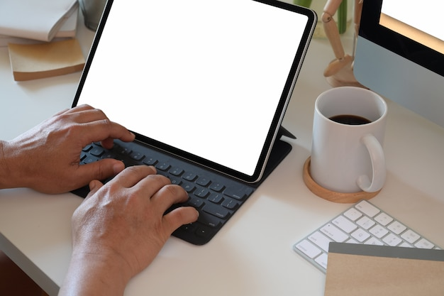 Businessman working with tablet and smart keyboard.