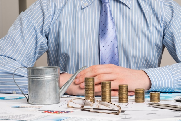 사업가 그의 책상에서 작동합니다. 사업가, 비즈니스 그래프 및 테이블에 돈