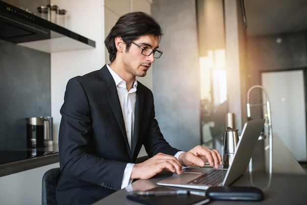 Бизнесмен работает от удаленного дома с ноутбуком из-за карантин коронавируса.