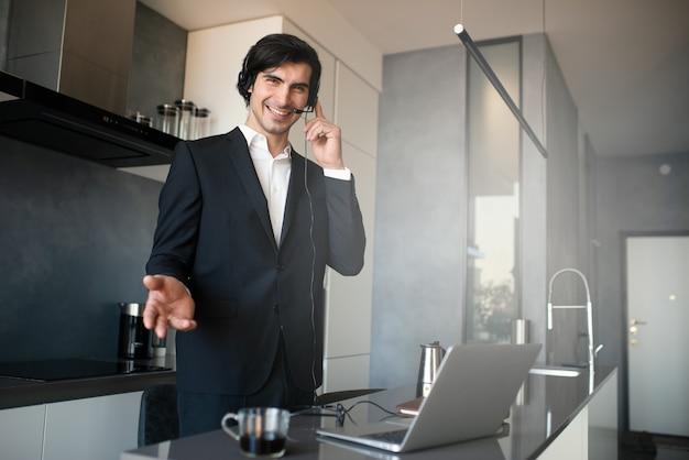 ビジネスマンは、コロナウイルス検疫のため、ラップトップを使用して自宅のリモートから作業します。