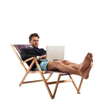Бизнесмен работает с компьютером на шезлонге