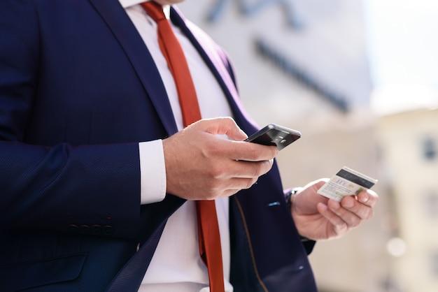 Бизнесмен работает с кредитной картой и телефоном