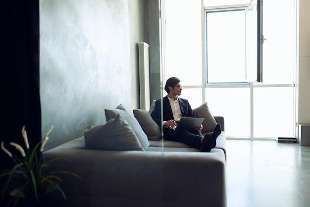 ビジネスマンは自宅で彼の現代のラップトップで動作します