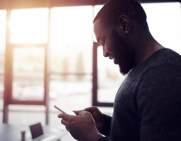 ビジネスマンはオフィスで彼のスマートフォンで動作します