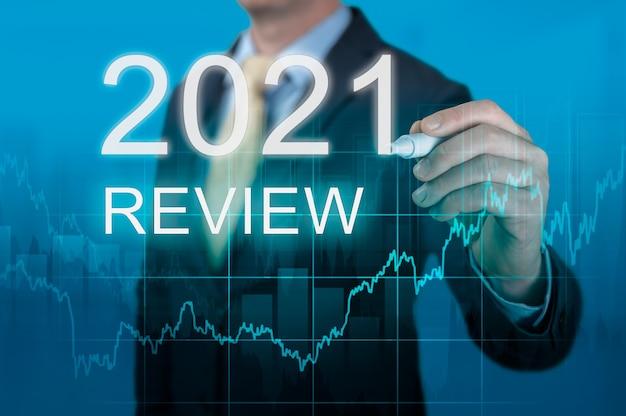 사업가는 2021년 리뷰 단어를 씁니다. 사업가는 가상 화면에 2021년 결과를 씁니다. 경제 지표, 위기 극복 및 2021년 코로나바이러스 전염병 이후 경제 회복