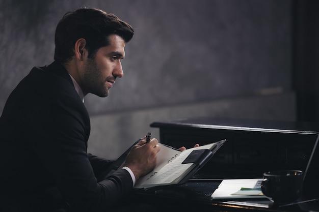 사업가 책상에 앉아있는 동안 노트북에 씁니다.