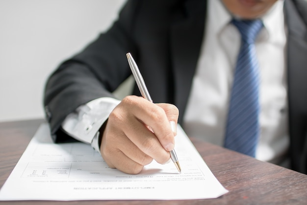 Businessman writing on application form and waiting for interview for get job