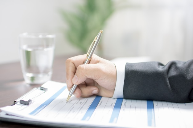 Businessman writing on application form or writing information.