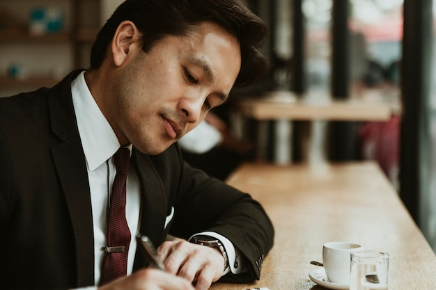 Businessman writing in a cafe