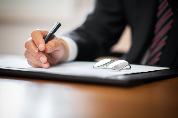 Businessman writing in a documen