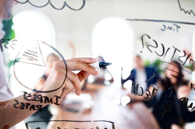 Businessman writing on a glass wall