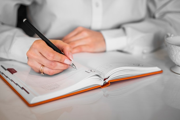 Businessman writing into notebook