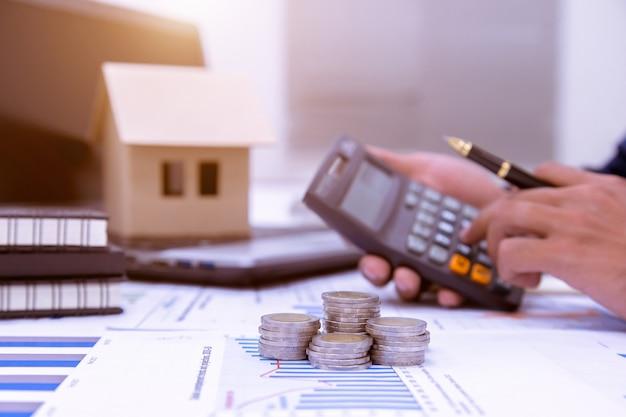 ビジネスマンは書き留めて、ホームオフィスで財務を計算します。