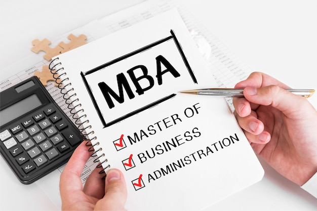 Businessman writing mba concepts on his note