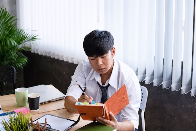 The businessman writing note on hard cover book, doing work,in office hour,hard work and busy,serious emotion