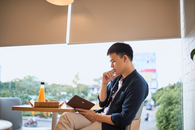 Businessman writing on notebook by cafe window, concentrated on work, side view of confident young man is working on notebook while sitting and writing in cafe,age 20-30 years.