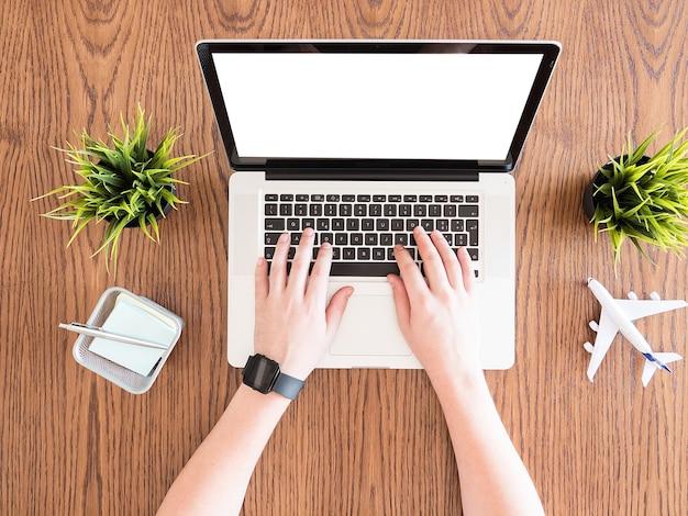 Woden 책상, 여행, 잔디 냄비, 메모에 자신의 노트북 개념 이미지에 쓰는 사업가