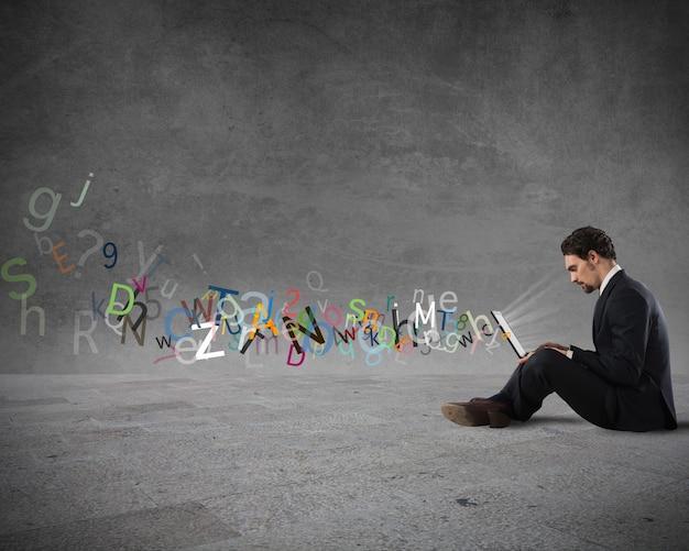 다채로운 단어의 편지 벽과 그의 노트북에 쓰는 사업가. 인터넷 채팅 및 통신의 개념