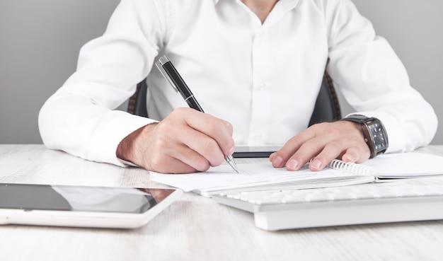 Бизнесмен писать на бумаге в офисе.