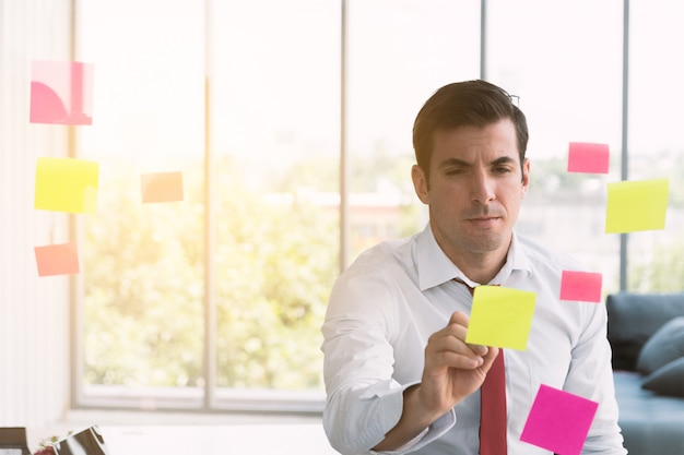 Businessman writing on post it at board.