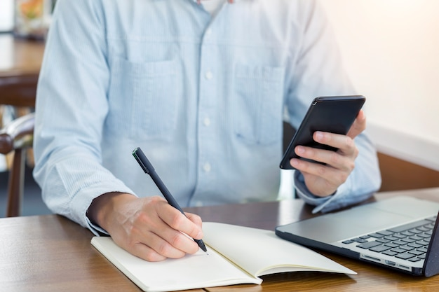 Предприниматель, пишущий что-то в записке или контрольном списке, используя смартфон с компьютером