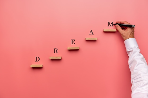 Businessman writing the word dream above wooden pegs placed in stairway like structure.