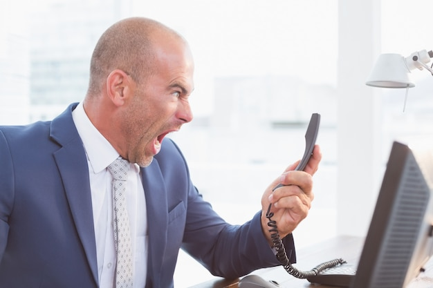 Businessman yelling at his phone