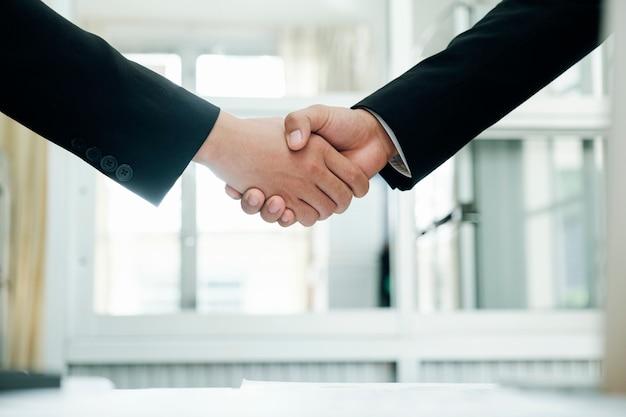 ビジネスマンはかなりの後に成功したビジネスマンの握手を握手します