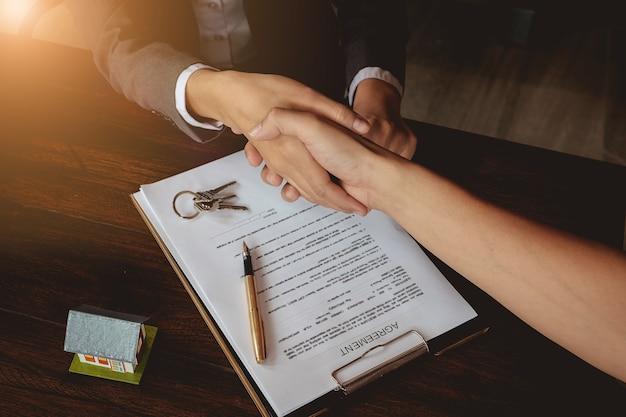 Businessmansハンドシェイク契約書にサインインした後の成功したビジネスマンハンドシェイク