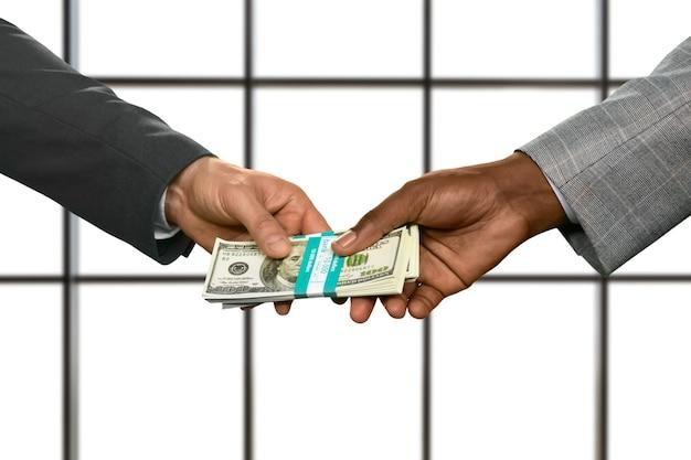 ビジネスマンの手がお金の束を渡す。白い背景でドルを取得します。お金が世界を支配します。道は奇妙な方向に曲がります。