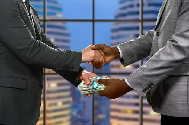 ビジネスマンの握手と送金。超高層ビルの横にある金融取引。シンプルで効果的なアプローチ。パートナーに注意してください。