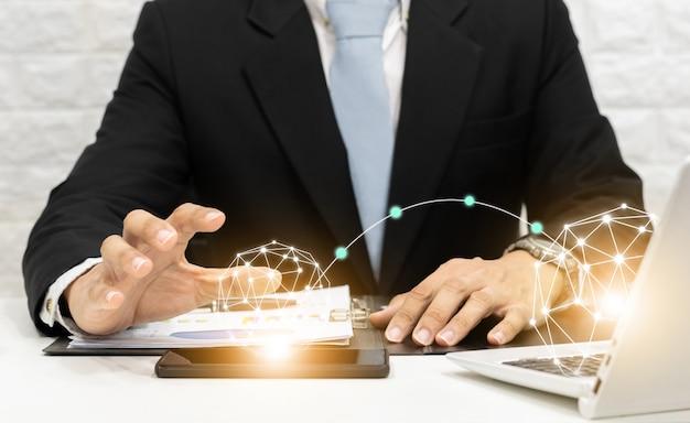 ビジネスマンは、コンピューター、スマートフォン、タブレットテクノロジーのソーシャルネットワークでグラフを分析します。