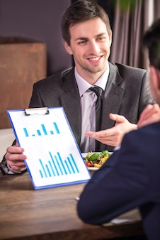 Businessmen analyzing graphs during a business lunch.
