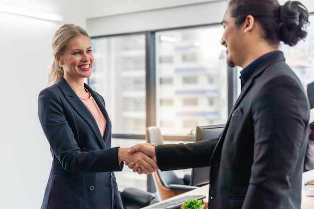 회의에 악수하는 기업인과 비즈니스 여자는 비즈니스에 대한 합의에 도달