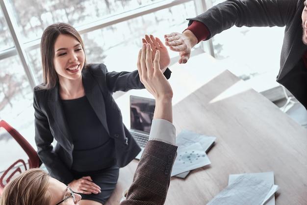 ビジネスマンとオフィスの実業家が一緒に働いてハイタッチの笑顔の幸せなクローズアップを与える