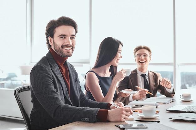 Бизнесмены и деловая женщина в офисе, работая вместе, сидя за столом, человек крупным планом, глядя в камеру, улыбается счастливым, в то время как коллеги пьют кофе, обсуждая смех проекта