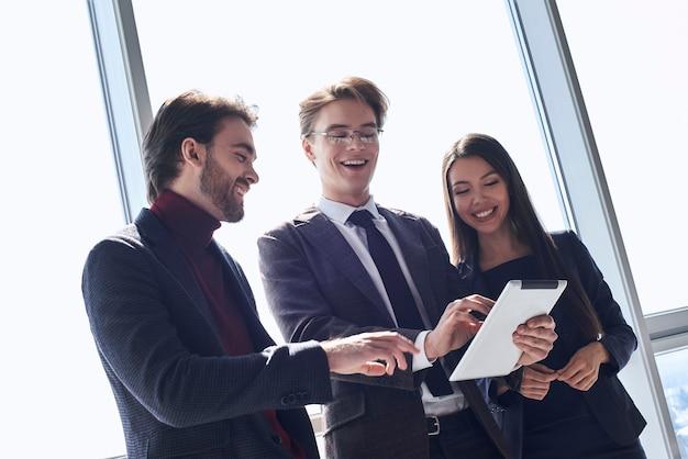 Бизнесмены и деловая женщина в офисе, работая вместе, стоя, просматривая цифровой планшет, улыбаясь, весело ищут новые идеи в интернете